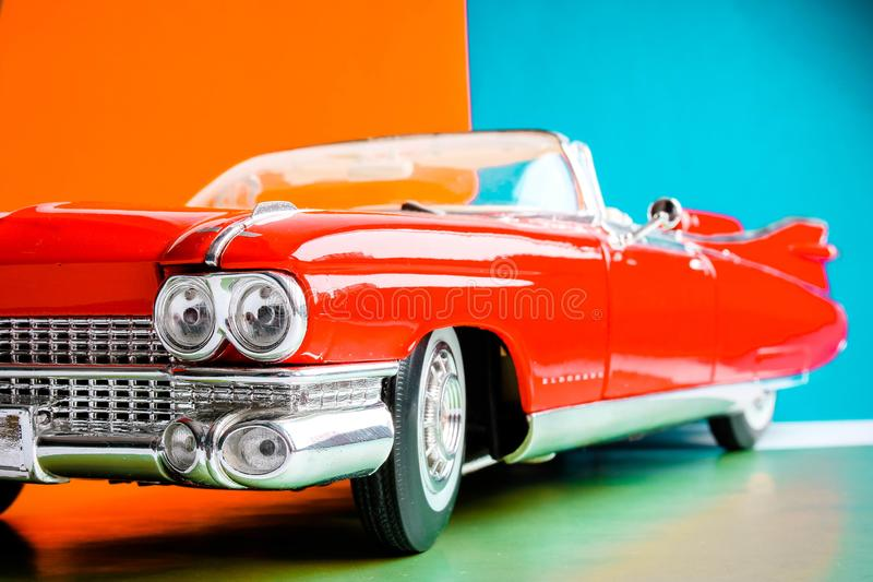 Vista ascendente próxima da capa e dos faróis Carro vermelho antigo dos E.U. Modelo à escala no fundo colorido fotografia de stock