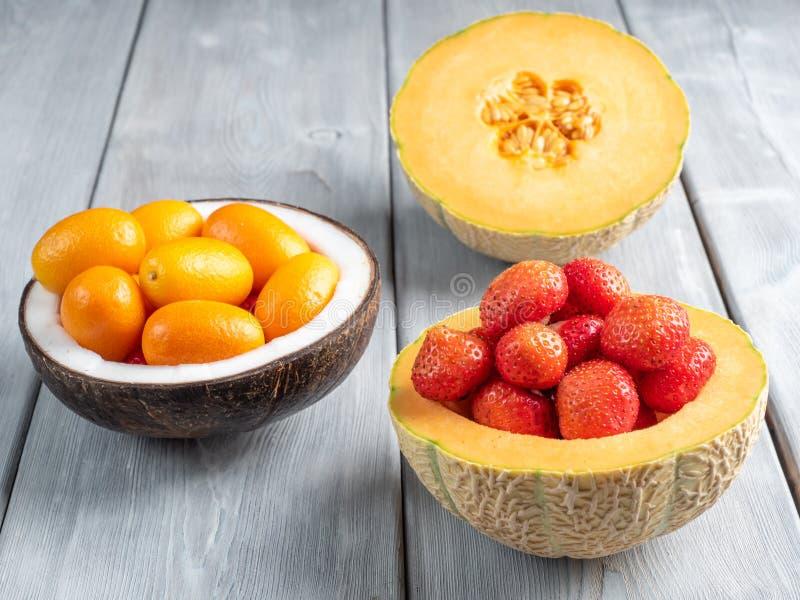 Vista ascendente próxima da morango no melão e no kumquat em uma bacia do coco e uma metade do melão no fundo de madeira branco fotos de stock royalty free