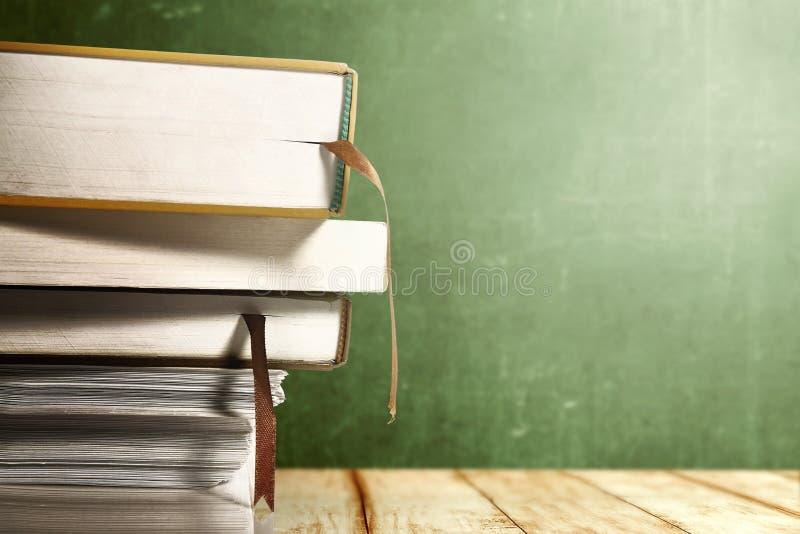 Vista ascendente próxima da pilha dos livros na tabela de madeira com fundo do quadro foto de stock
