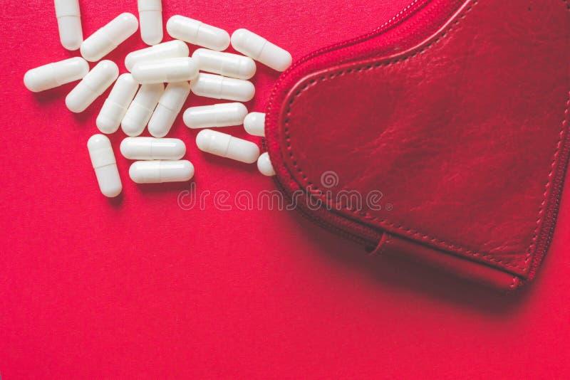 Vista ascendente próxima das cápsulas brancas que derramam uma carteira dada forma coração no fundo vermelho fotografia de stock