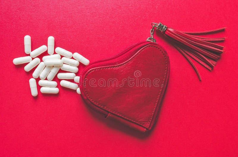 Vista ascendente próxima das cápsulas brancas que derramam uma carteira dada forma coração no fundo vermelho imagens de stock