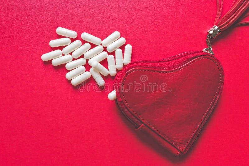 Vista ascendente próxima das cápsulas brancas que derramam uma carteira dada forma coração no fundo vermelho imagem de stock royalty free
