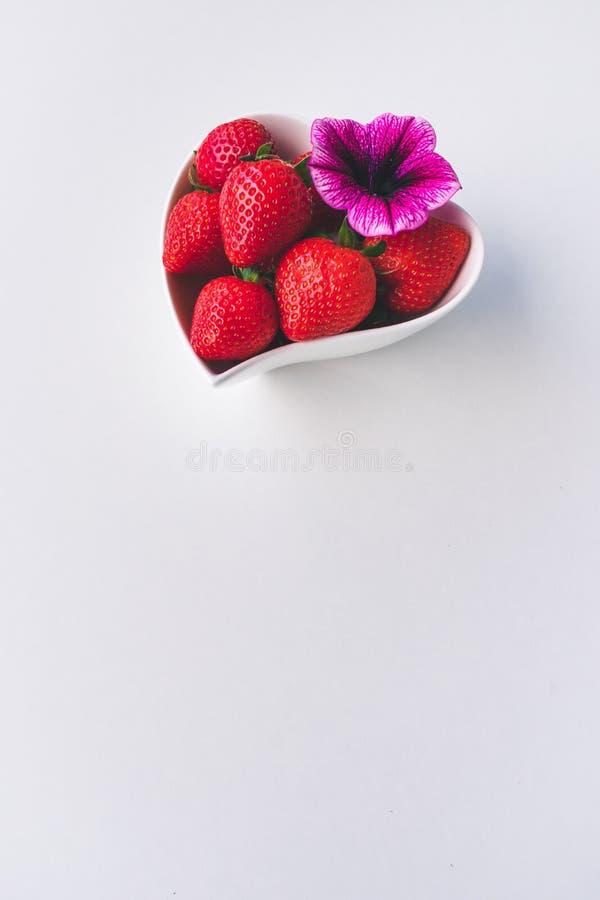 Vista ascendente pr?xima das morangos e de uma flor cor-de-rosa cora??o branco em uma bacia dada forma no fundo branco imagem de stock royalty free