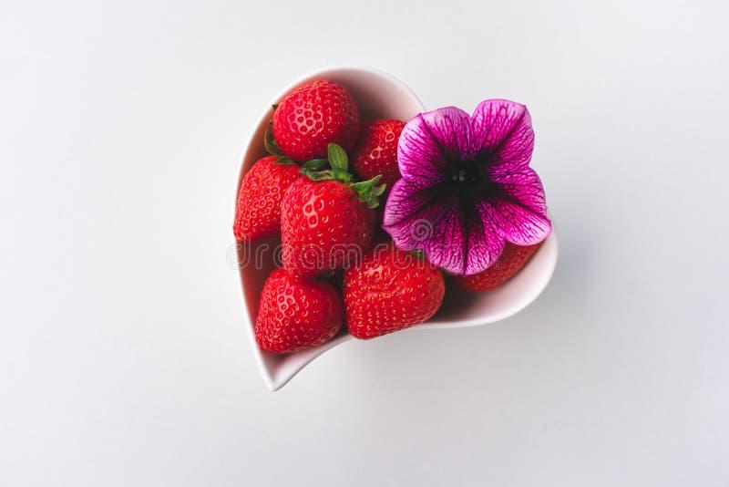 Vista ascendente pr?xima das morangos e de uma flor cor-de-rosa cora??o branco em uma bacia dada forma no fundo branco fotografia de stock royalty free