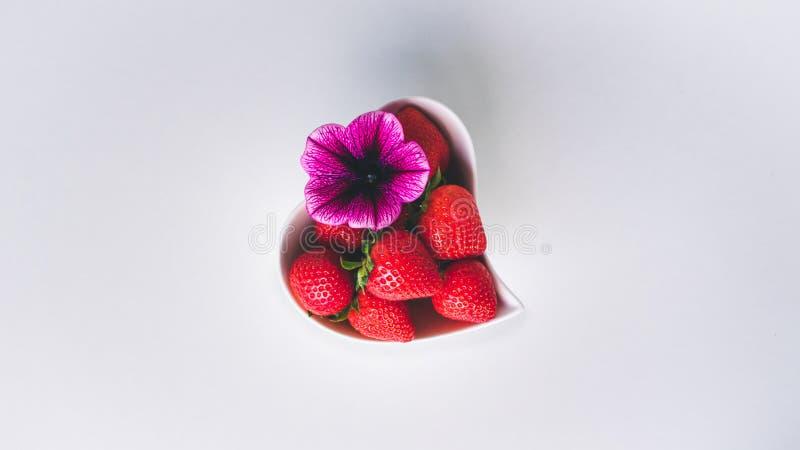 Vista ascendente pr?xima das morangos e de uma flor cor-de-rosa cora??o branco em uma bacia dada forma no fundo branco fotos de stock