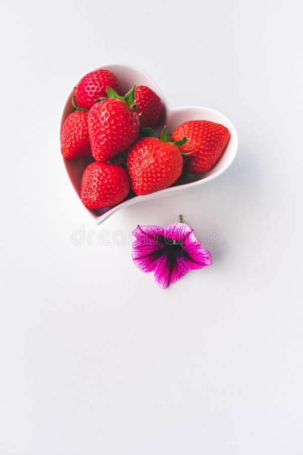 Vista ascendente pr?xima das morangos e de uma flor cor-de-rosa cora??o branco em uma bacia dada forma no fundo branco imagens de stock