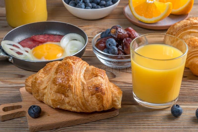 Vista ascendente próxima de um almoço completo com croissant e Fried Eggs e suco de laranja imagens de stock royalty free