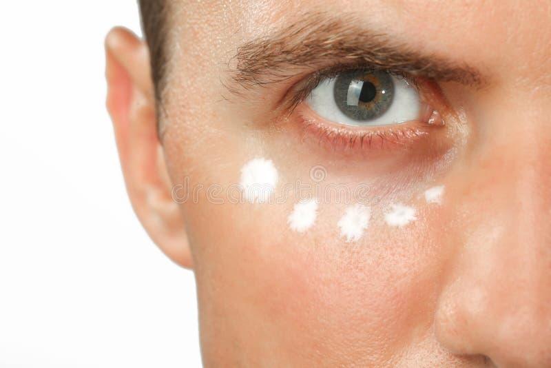 Vista ascendente próxima de um olho do homem verde, tratamento do creme do olho foto de stock