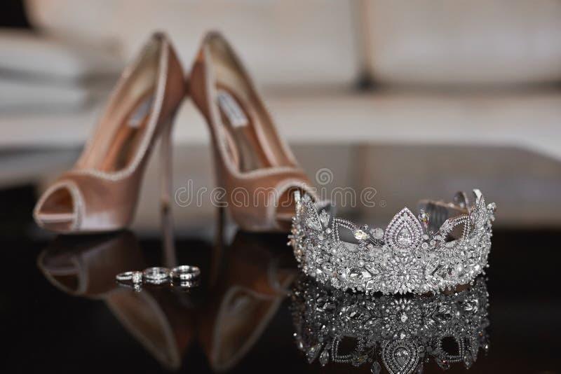 Vista ascendente próxima do diadema luxuoso do casamento da platina com diamantes e as sapatas fêmeas do casamento antes da cer fotografia de stock