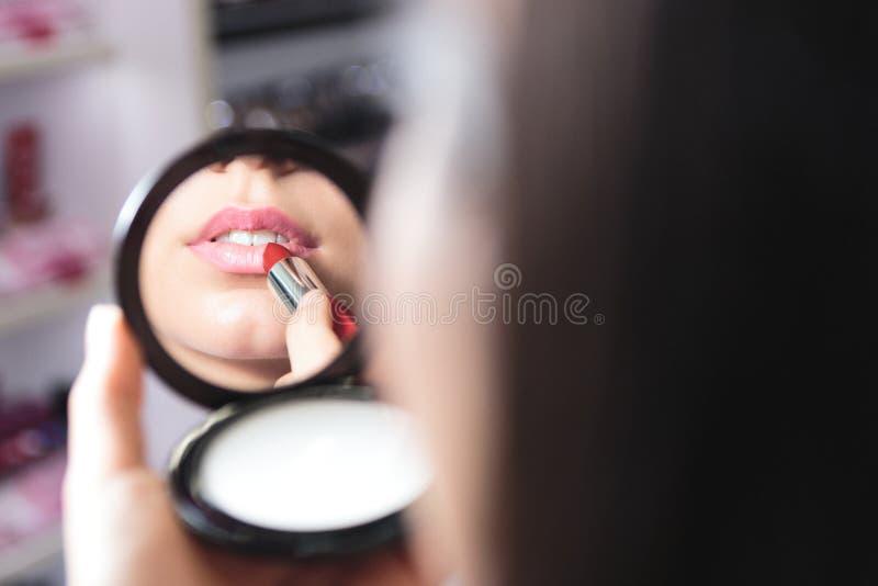 A vista ascendente próxima dos bordos da mulher e o batom aplicam-se em um espelho pequeno foto de stock royalty free