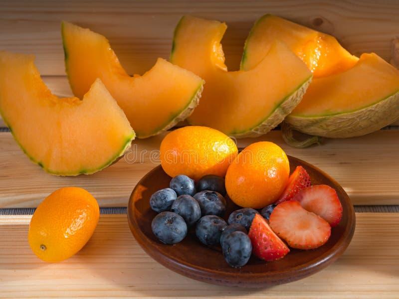 Vista ascendente próxima dos mirtilos e as morangos e o melão e o kumquat em um fundo de madeira iluminado pela luz solar Foco ma foto de stock royalty free
