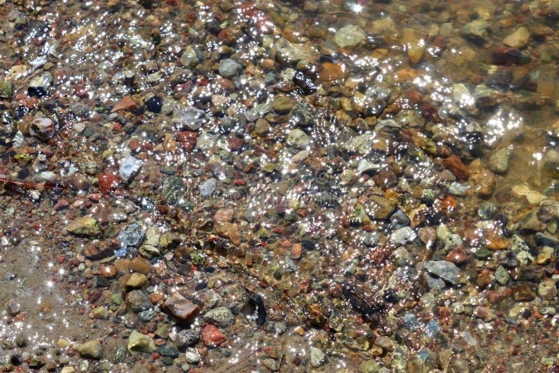 Vista ascendente próxima em uma superfície reflexiva da água com ondas e ondinhas na alta resolução imagens de stock