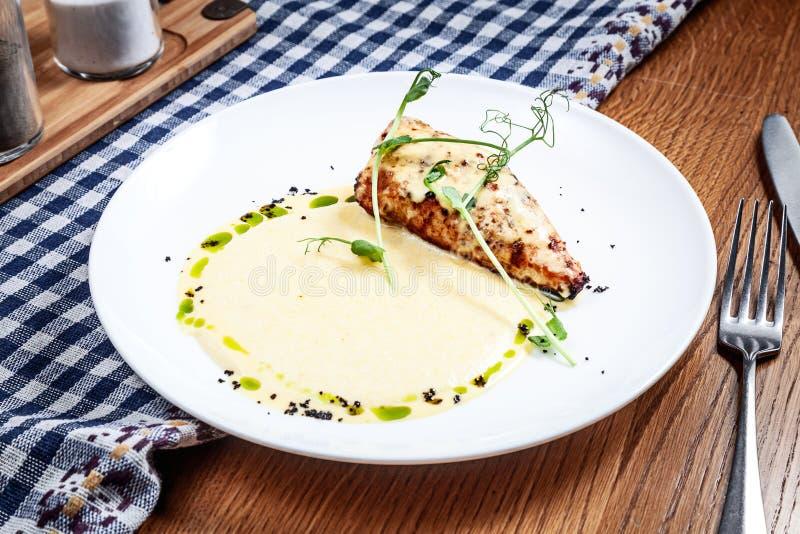 Vista ascendente pr?xima na faixa servida da galinha com molho do polenta e do milho no fundo de madeira Culin?ria moderna Copie  fotografia de stock