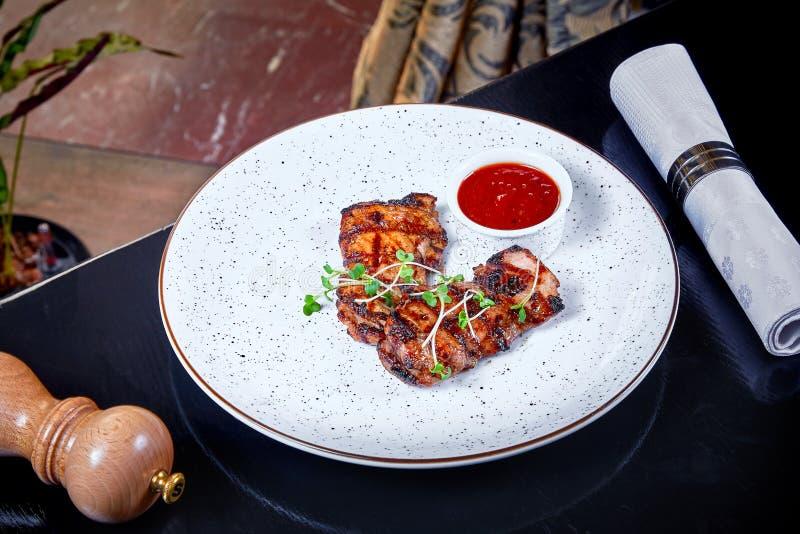 Vista ascendente próxima na parcela de galinha grelhada com molho vermelho na placa branca Fundo do alimento do restaurante Prato imagens de stock