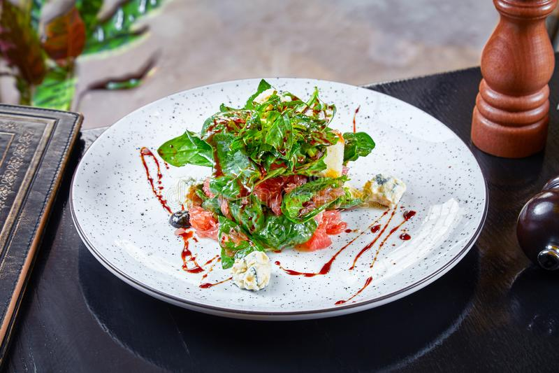 Vista ascendente próxima na salada com espinafres, queijo azul e toranja no fundo escuro Culin?ria moderna Alimento saud?vel para fotos de stock