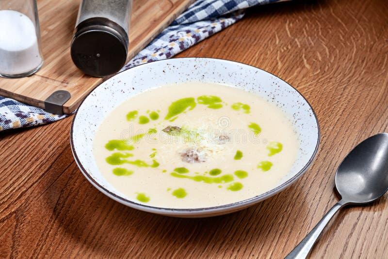 Vista ascendente próxima na sopa do creme da batata com o mitboli com o pesto servido na placa cinzenta na tabela de madeira marr imagens de stock