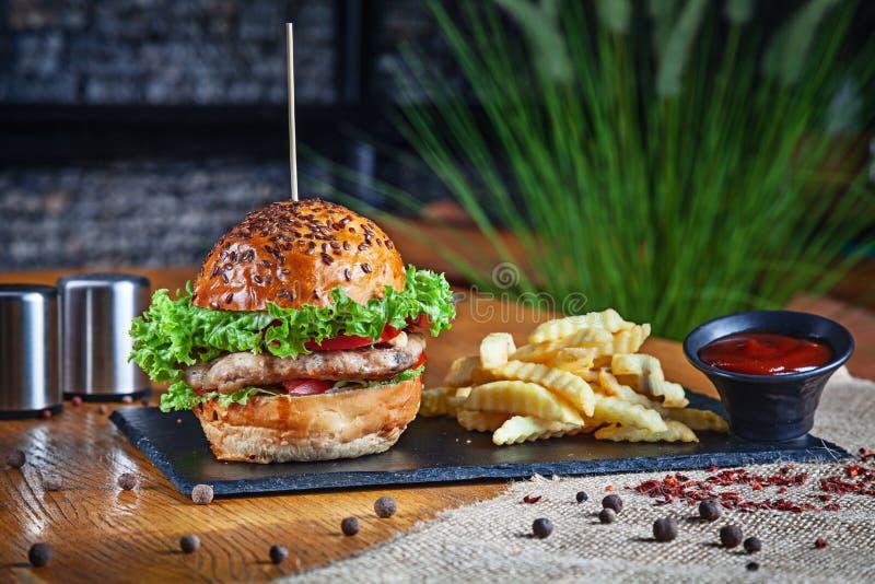 Vista ascendente próxima no hamburguer americano clássico Hamburguer da galinha com batatas fritas e molho vermelho Fast food ins foto de stock royalty free