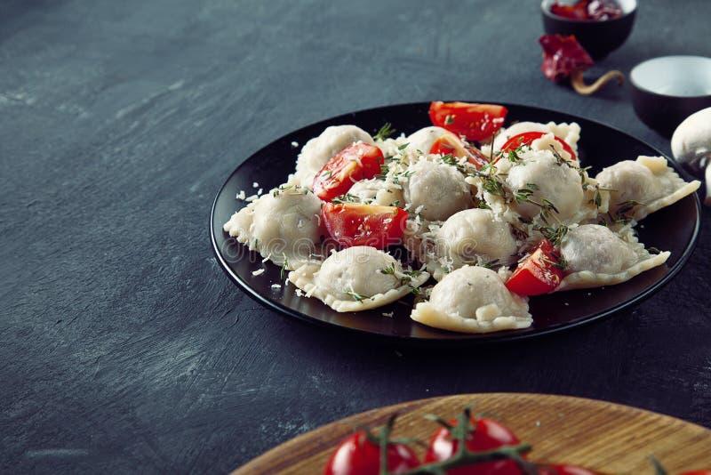 Vista ascendente próxima no ravioli fresco com o tomate de cereja da fatia na placa preta e no fundo escuro fotografia de stock