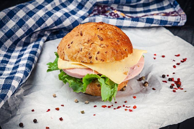 Vista ascendente próxima no sanduíche com presunto, alface, tomate no fundo branco com espaço da cópia Fast food snack Alimento p foto de stock