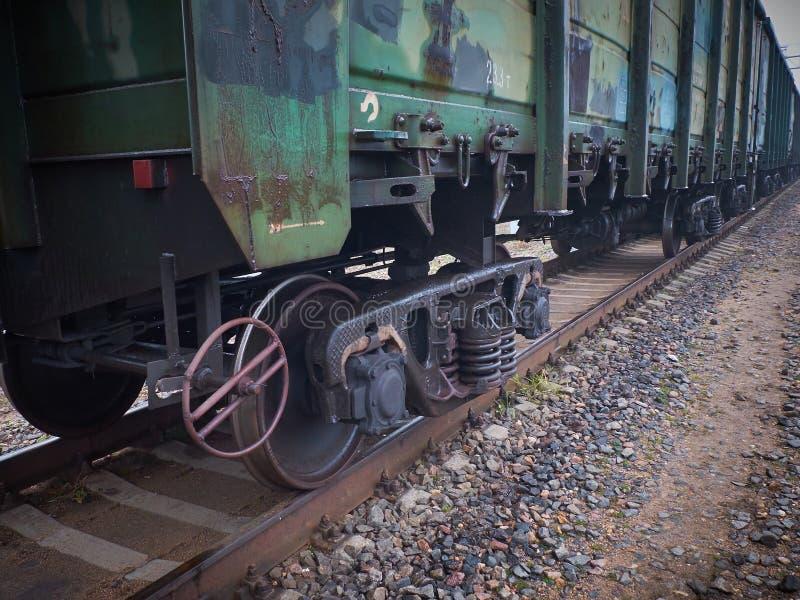Vista ascendente próxima no vagão oxidado usado do carro de frete da estrada de ferro com rodas com axleboxes, molas de bobina Tr imagens de stock royalty free