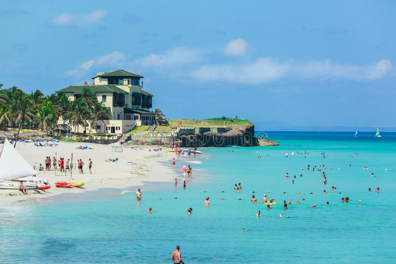 Vista asombrosa de la playa cubana magnífica ocupada con mucha gente que nada en el océano fotos de archivo libres de regalías