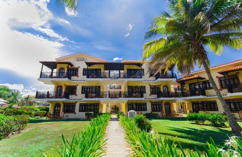 Vista asombrosa de los argumentos coloniales del hotel, edificios elegantes retros de invitación hermosos en jardín tropical foto de archivo libre de regalías