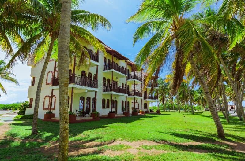 Vista asombrosa de los argumentos coloniales del hotel, edificios elegantes retros de invitación hermosos en jardín tropical en e imagen de archivo libre de regalías