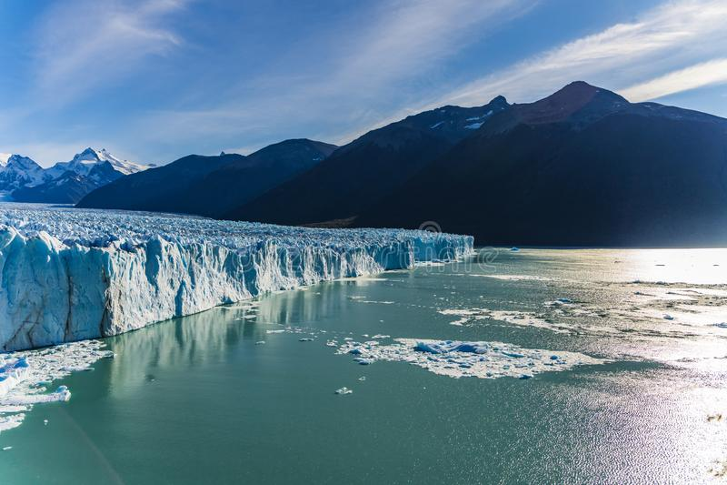 Vista asombrosa del glaciar de Perito Moreno, glaciar azul del burg del hielo con la luz de oro del sol shinning a través del lag fotografía de archivo libre de regalías