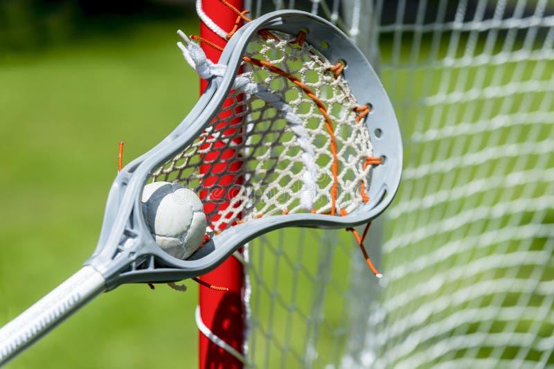 Vista astratta di un bastone di lacrosse che scava su una palla immagine stock libera da diritti