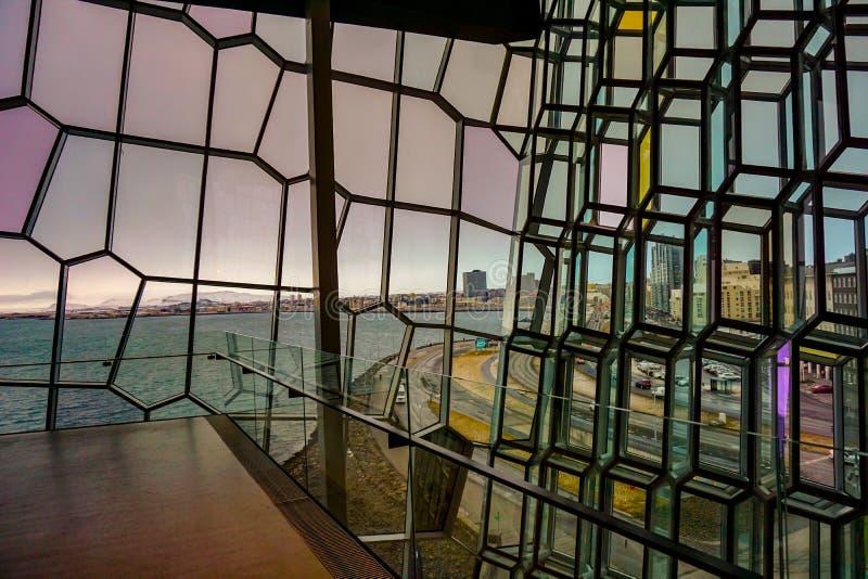 Vista através da fachada de vidro do Harpa, com a cidade de Reykjavik no fundo imagem de stock royalty free