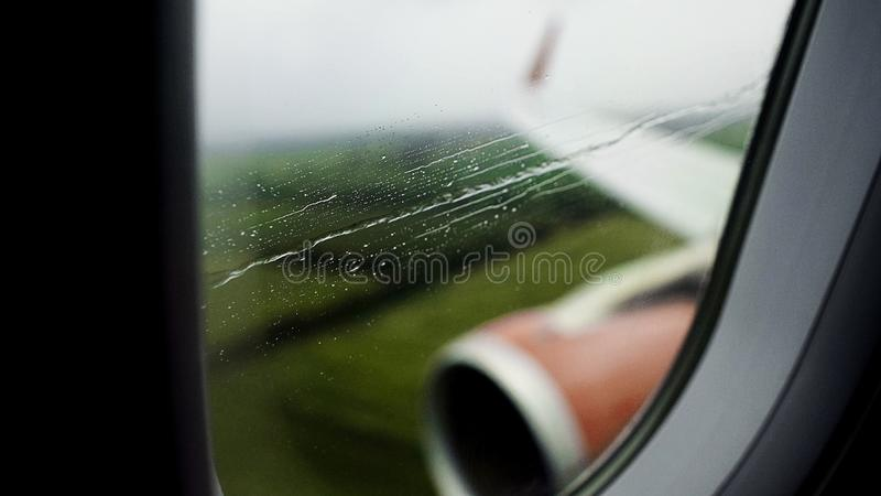 Vista através da janela chuvosa do avião que aterra com sucesso a pista de decolagem no aeroporto foto de stock