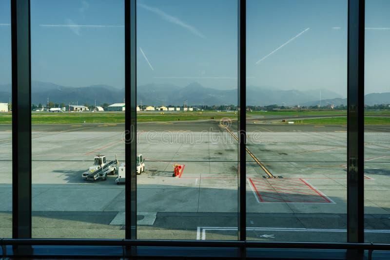 Vista através da janela terminal da partida do aeroporto à pista de decolagem fotografia de stock royalty free