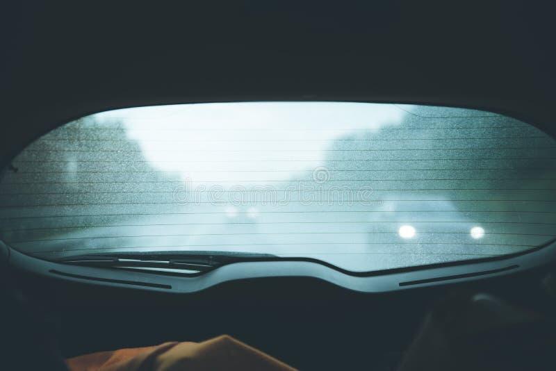 Vista através da janela traseira de um carro, dia chuvoso imagens de stock