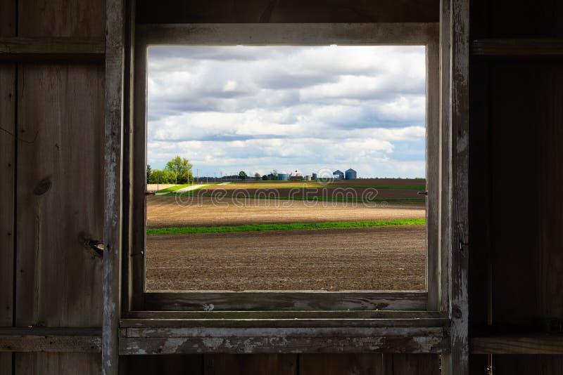 Vista através da janela velha do celeiro imagem de stock royalty free