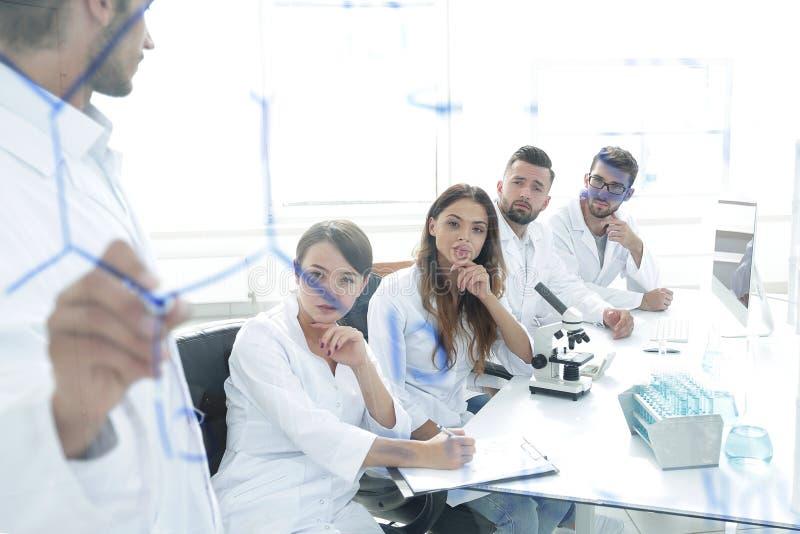 Vista através da placa transparente um cientista faz um relatório foto de stock