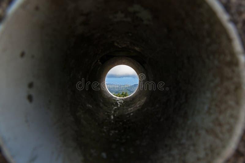 Vista através da tubulação na paisagem com montes e oceano fotografia de stock royalty free