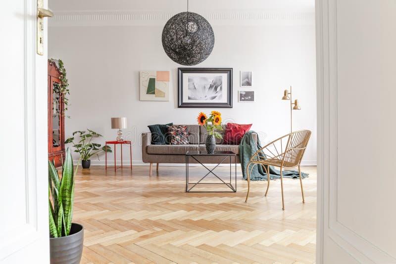 Vista através de um estar aberto em um interior da sala de visitas com mobília eclético e em um assoalho de folhosa espaçosos, or fotos de stock