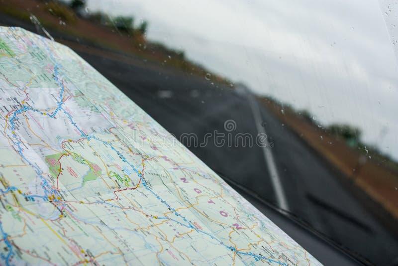 Vista através de um para-brisa com um mapa de estradas no painel fotografia de stock royalty free