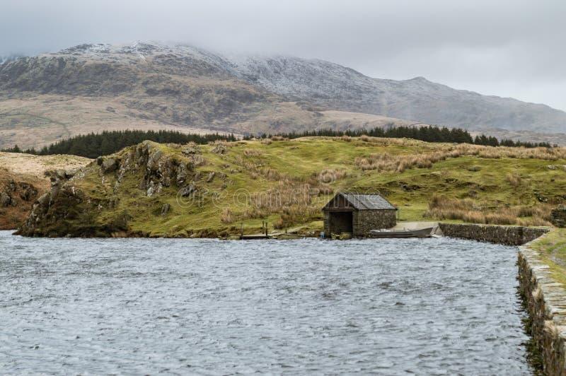 Vista através do lago à ferradura de Snowdon e do estaleiro em Llyn Dywarchen no parque nacional de Snowdonia imagens de stock