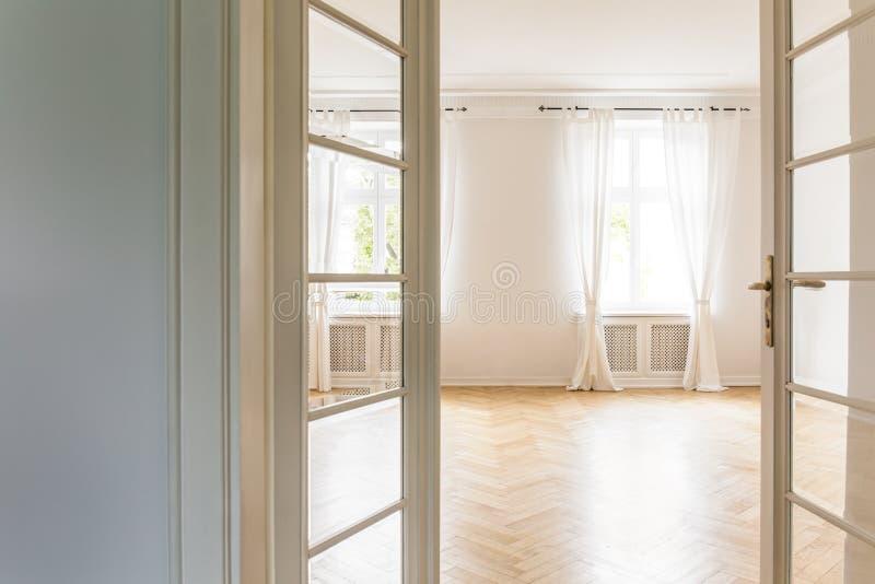 Vista attraverso la porta di vetro aperta su un interio vuoto e luminoso della camera da letto fotografia stock libera da diritti
