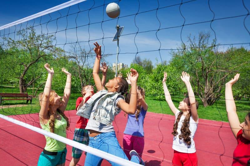Vista attraverso la rete di pallavolo di gioco degli anni dell'adolescenza fotografia stock libera da diritti
