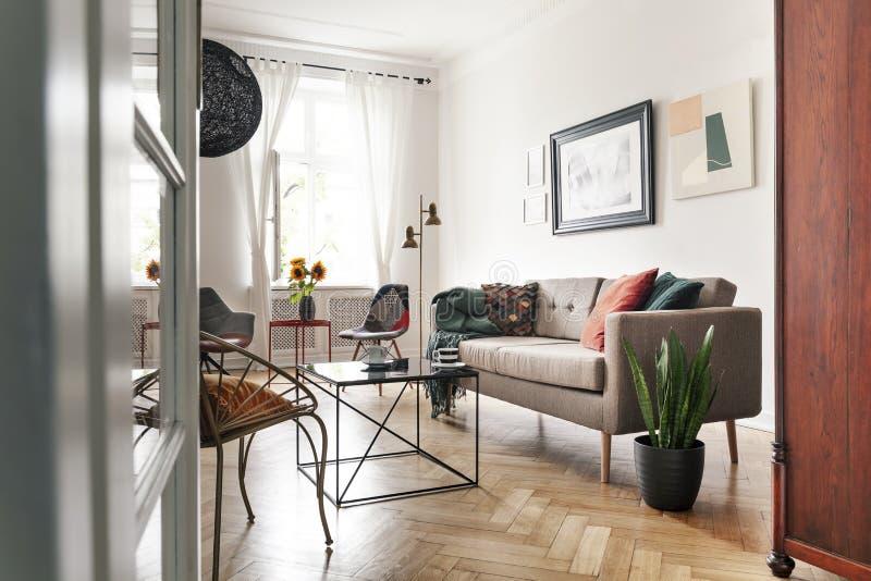 Vista attraverso una porta di vetro aperta su un interno luminoso del salone con la mobilia mista di stile e una finestra alta co immagini stock libere da diritti
