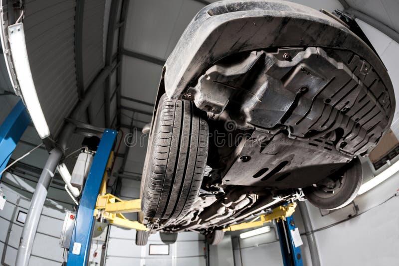 Vista automatica dal fondo Sospensione anteriore dell'automobile il meccanico del garage ha alzato l'automobile sull'ascensore immagini stock libere da diritti