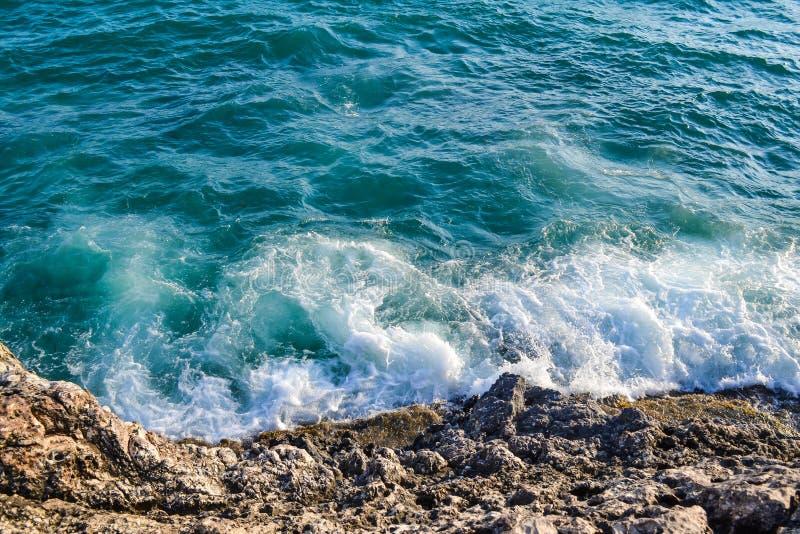Vista azul do mar com uma onda branca, pulverizador na rocha da praia A onda bate a costa imagem de stock royalty free