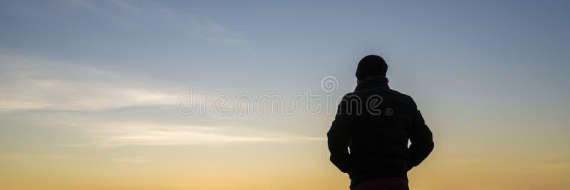 Vista backlit larga na pessoa com mãos em uns bolsos fotografia de stock royalty free