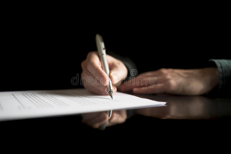 Vista bassa di firma della mano dell'uomo d'affari legale o del documento di assicurazione fotografia stock