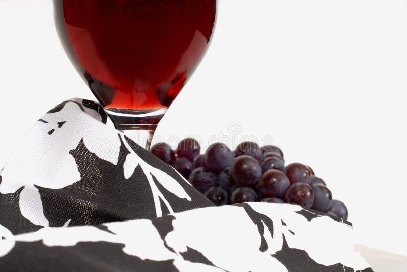 Vista bassa di un vetro di vino con vino ed uva e tovagliolo fotografia stock libera da diritti