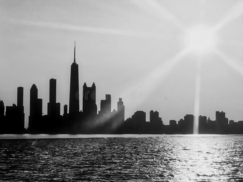 Vista in bianco e nero dell'orizzonte di Chicago veduta dal lago Michigan, con il tramonto ed i raggi di sole che estendono sopra fotografia stock libera da diritti