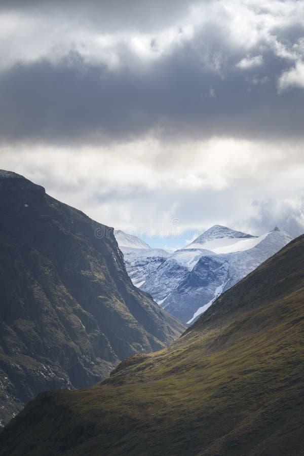 A vista bonita através do vale da montanha com na neve e das geleiras cobriu a cordilheira de Scandes imagem de stock