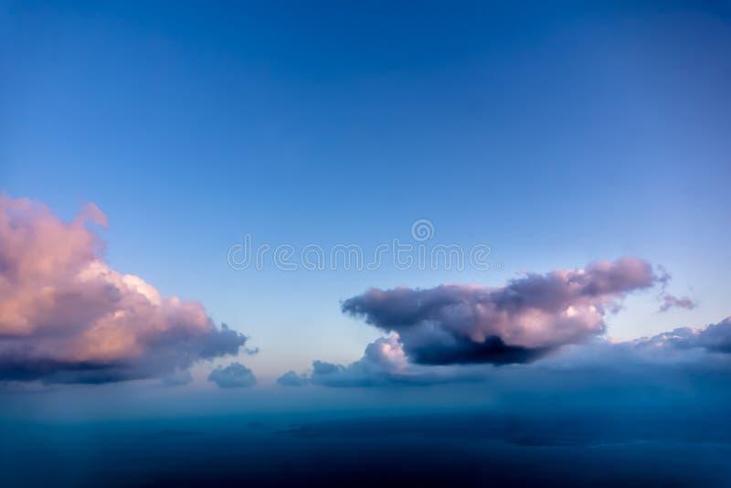 Vista bonita da janela do avião - nuvens azuis róseos brancas foto de stock royalty free